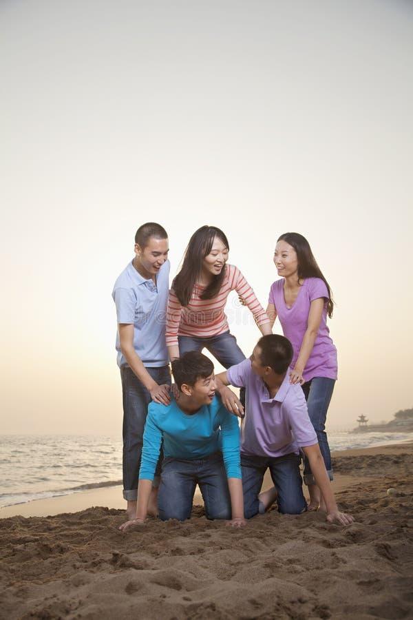 Grupp av vänner som gör den mänskliga pyramiden på stranden arkivfoton