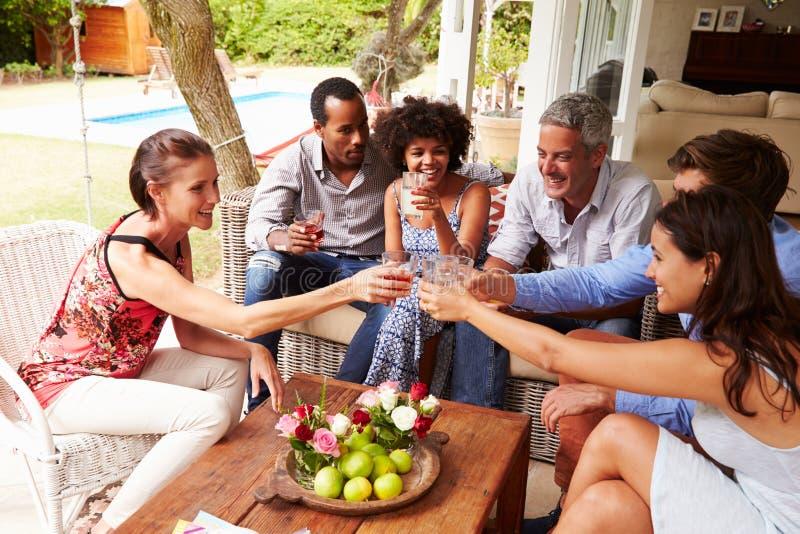 Grupp av vänner som gör ett celebratory rostat bröd i drivhus royaltyfri foto