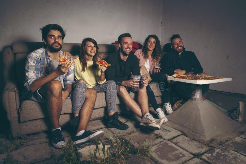 Grupp av vänner som håller ögonen på en film arkivfoton