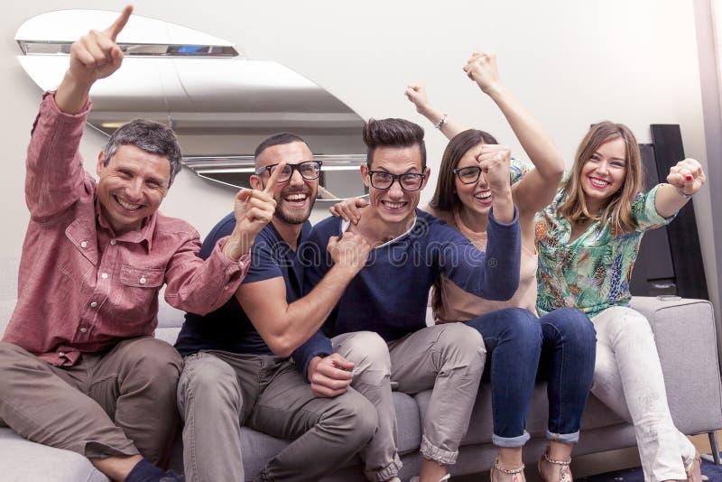 Grupp av vänner som håller ögonen på en fotbollsmatch på tv royaltyfri foto