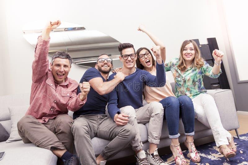 Grupp av vänner som håller ögonen på en fotbollsmatch på tv royaltyfria bilder