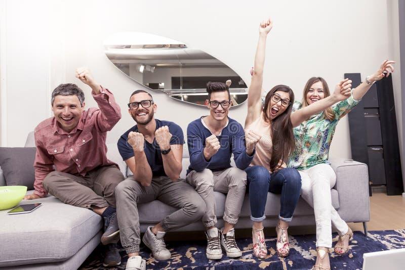 Grupp av vänner som håller ögonen på en fotbollsmatch på tv på soffan royaltyfri bild