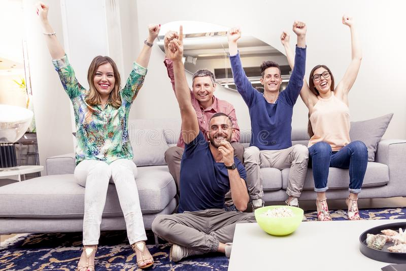 Grupp av vänner som håller ögonen på en fotbollsmatch på tv på soffan royaltyfri foto