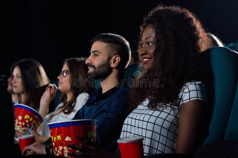 Grupp av vänner som håller ögonen på filmer på den lokala bion arkivfoton