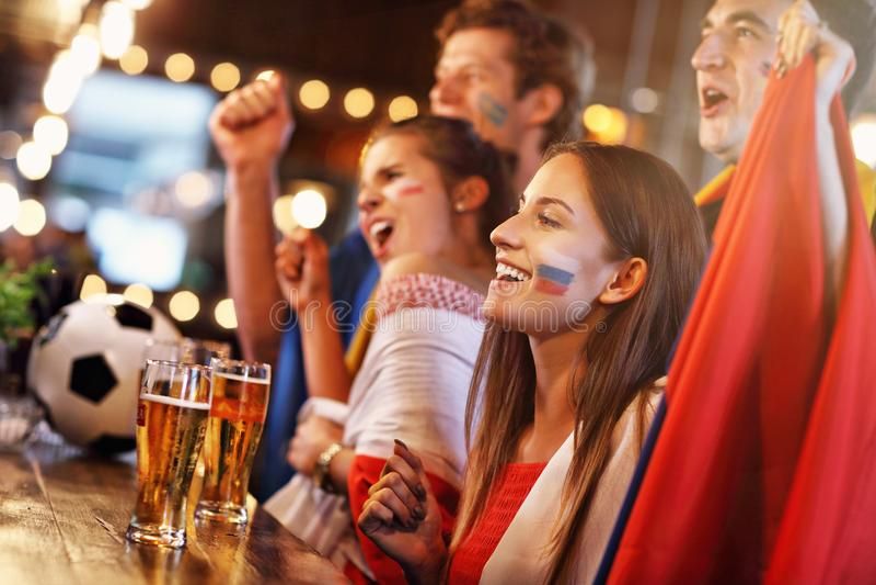 Grupp av vänner som håller ögonen på fotboll i bar royaltyfri fotografi