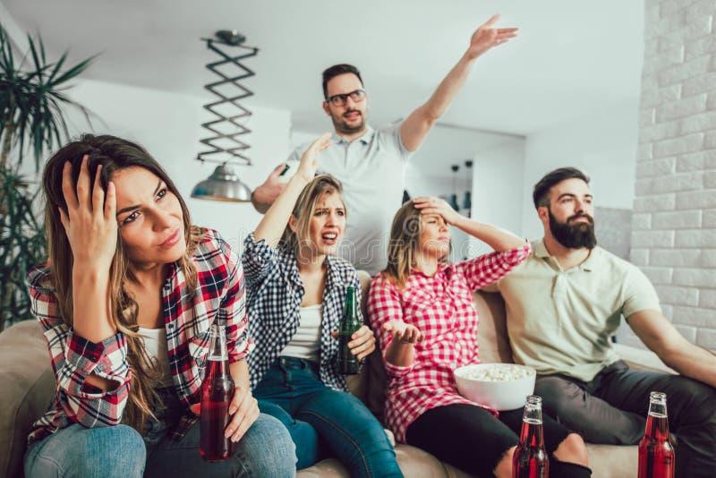 Grupp av vänner som håller ögonen på TV att matcha royaltyfri bild