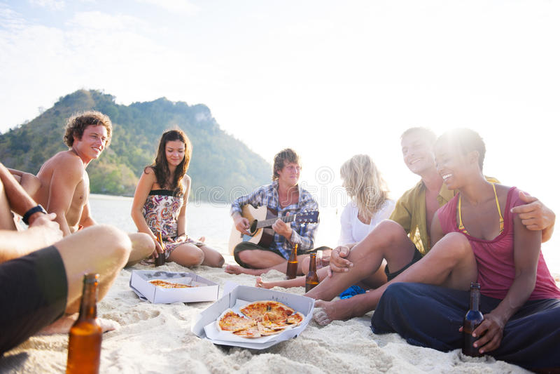 Grupp av vänner som har ett sommarstrandparti royaltyfri fotografi