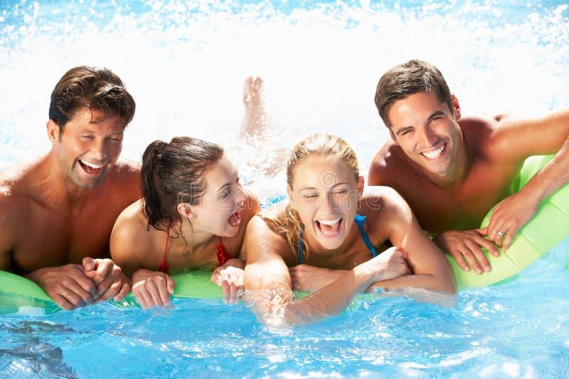 Grupp av vänner som har gyckel i simbassäng royaltyfri bild