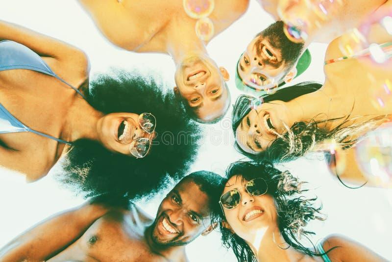 Grupp av vänner som har gyckel som ler att se ner på kameran ungdomari strandkläder som tycker om göra toothy leenden Begrepp av arkivfoto