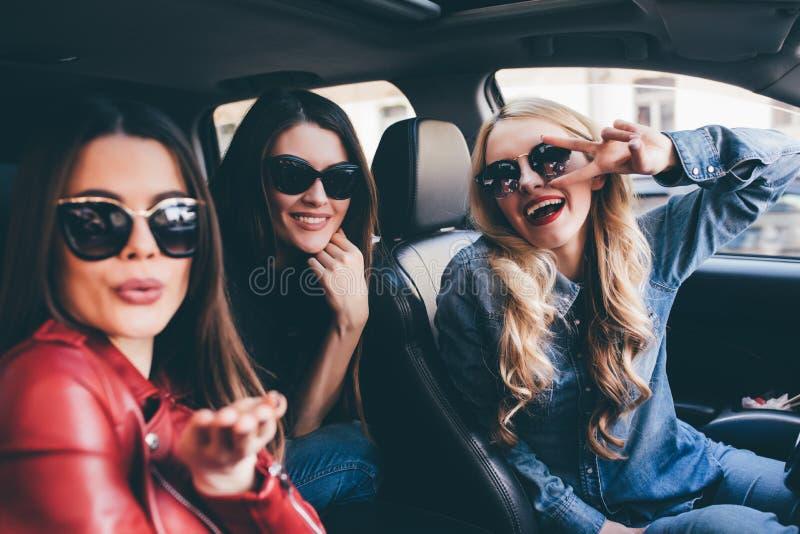 Grupp av vänner som har gyckel på bilen Sjunga och skratta i staden arkivbild