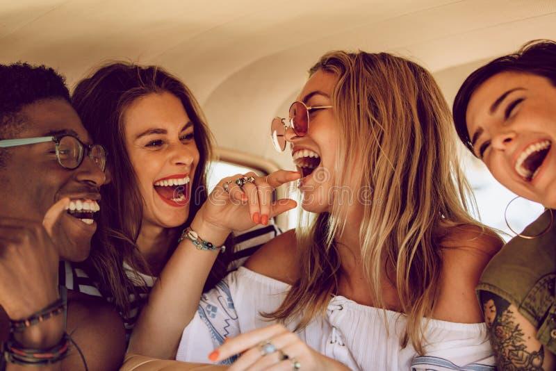 Grupp av vänner som har gyckel på en vägtur arkivbild