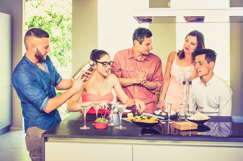 Grupp av vänner som har gyckel på huspartiet med pre matställeaperi arkivfoto