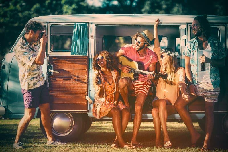 Grupp av vänner som har gyckel på musikfestivalen royaltyfri bild