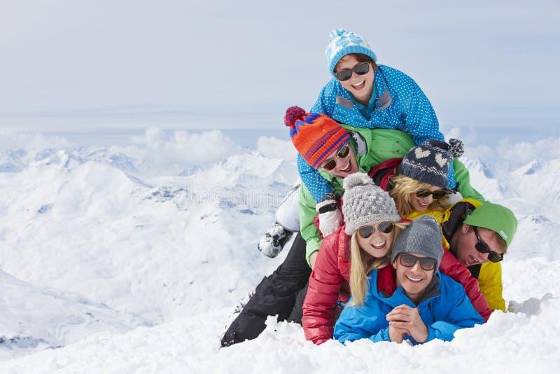 Grupp av vänner som har gyckel på Ski Holiday In Mountains royaltyfria foton
