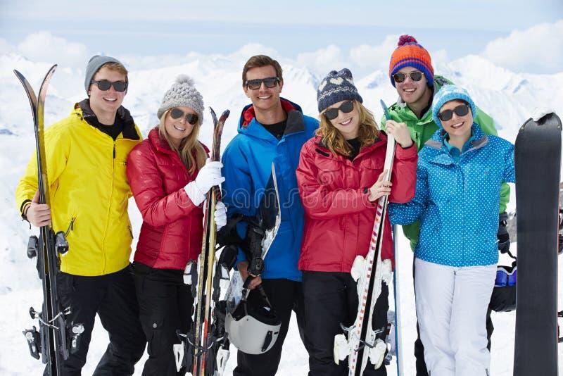 Grupp av vänner som har gyckel på Ski Holiday In Mountains arkivfoton