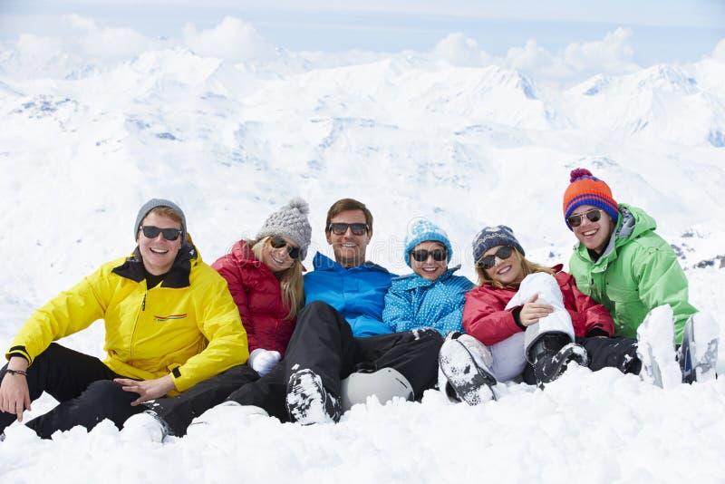 Grupp av vänner som har gyckel på Ski Holiday In Mountains royaltyfri fotografi