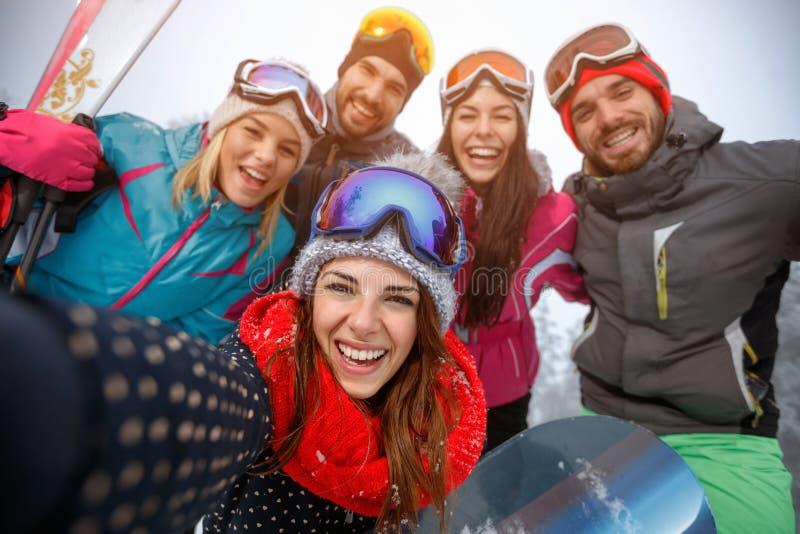Grupp av vänner som har gyckel på snön och gör selfie fotografering för bildbyråer