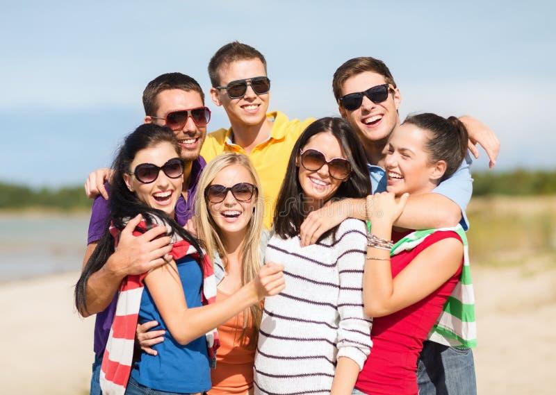 Grupp av vänner som har gyckel på stranden arkivbilder
