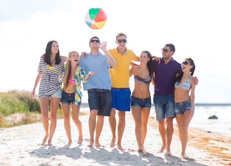 Grupp av vänner som har gyckel på stranden arkivbild