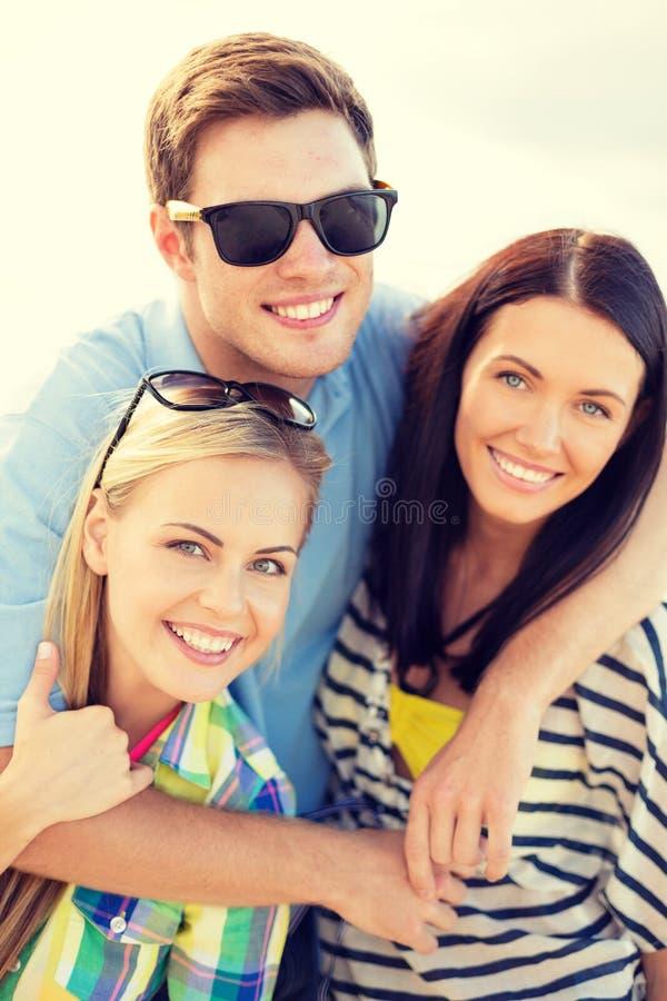 Grupp av vänner som har gyckel på stranden royaltyfri foto