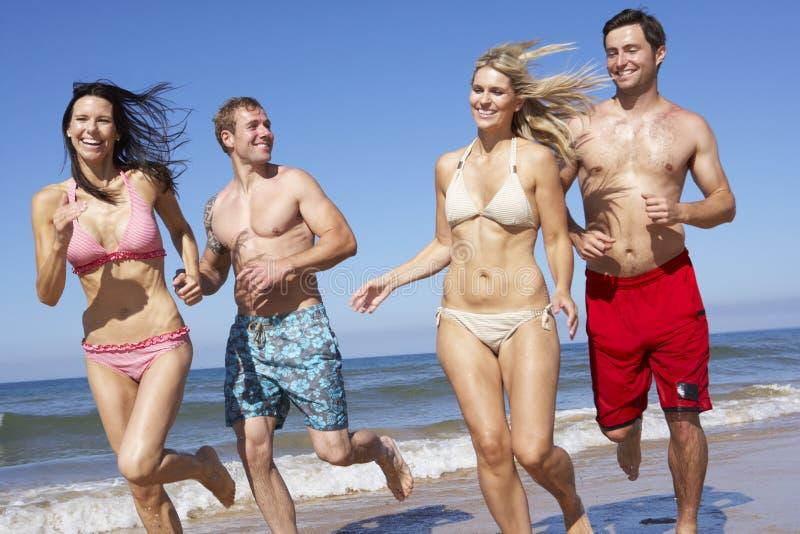 Grupp av vänner som har gyckel på strandferie tillsammans fotografering för bildbyråer