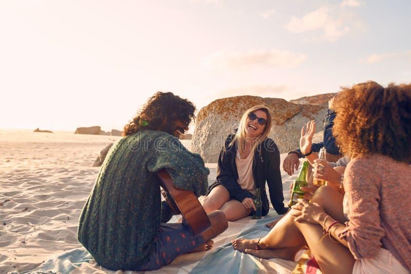 Grupp av vänner som har gyckel på strandpartiet arkivfoton