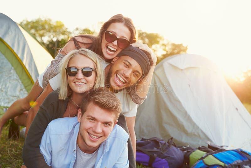 Grupp av vänner som har gyckel utanför tält på campa ferie arkivfoto