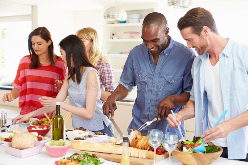 Grupp av vänner som har matställepartiet hemma royaltyfri bild