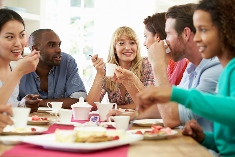 Grupp av vänner som har ost och kaffe på matställepartiet arkivfoto