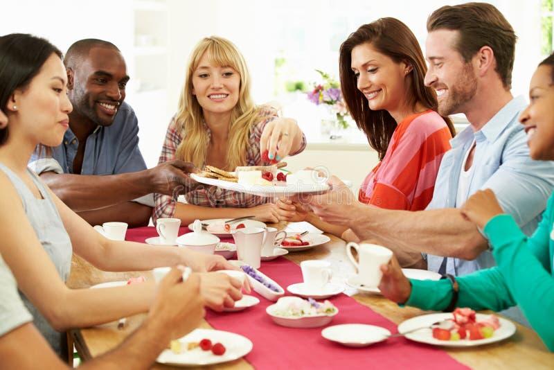 Grupp av vänner som har ost och kaffe på matställepartiet royaltyfria foton