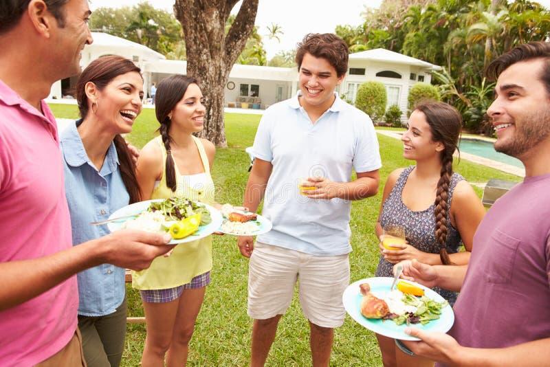 Grupp av vänner som har partiet i trädgård hemma royaltyfri foto