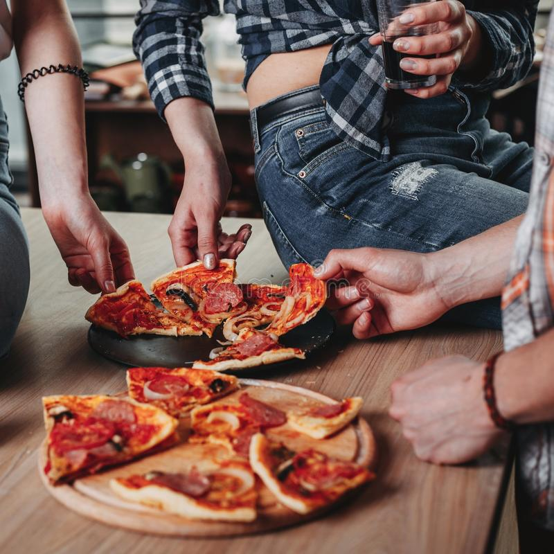 Grupp av vänner som har partiet och äter pizza royaltyfri foto
