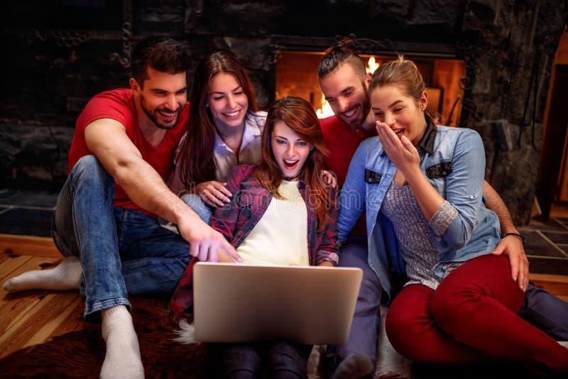 Grupp av vänner som har rolig hållande ögonen på film tillsammans på bärbara datorn arkivfoto