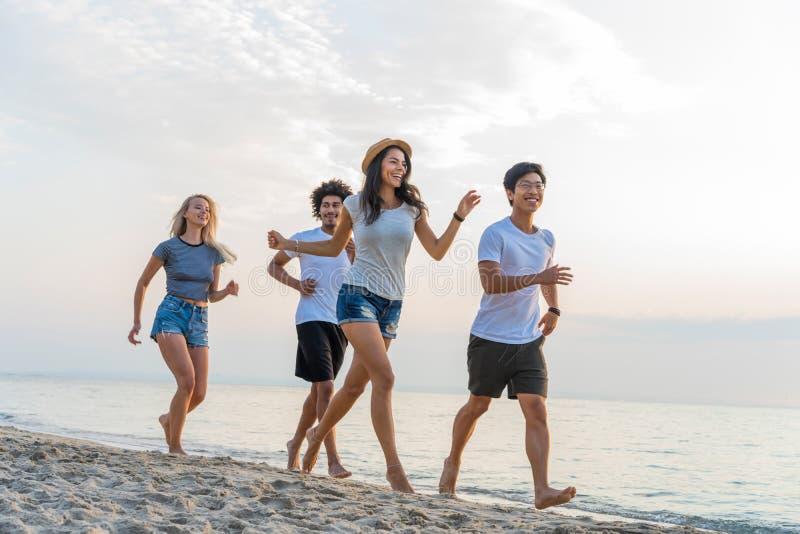 Grupp av vänner som har rolig spring ner stranden på solnedgången royaltyfri foto