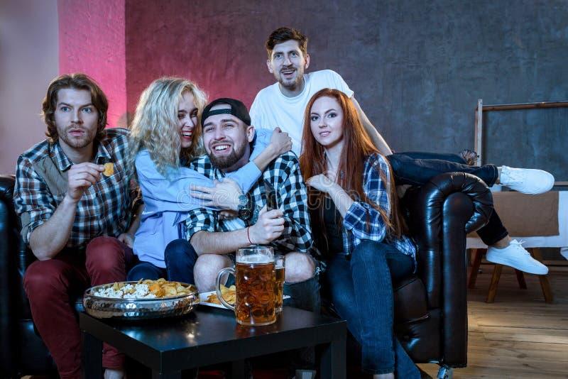 Grupp av vänner som har roligt hemmastatt, hålla ögonen på som är modigt, och tycka om t fotografering för bildbyråer