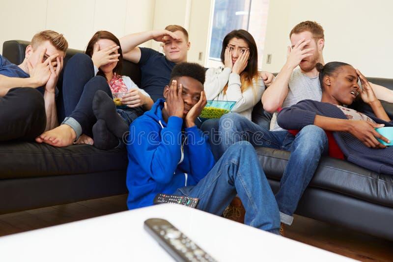 Grupp av vänner som hemma håller ögonen på television tillsammans royaltyfri fotografi