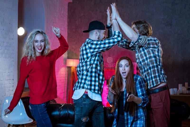 Grupp av vänner som hemma håller ögonen på TVmatchen royaltyfri fotografi