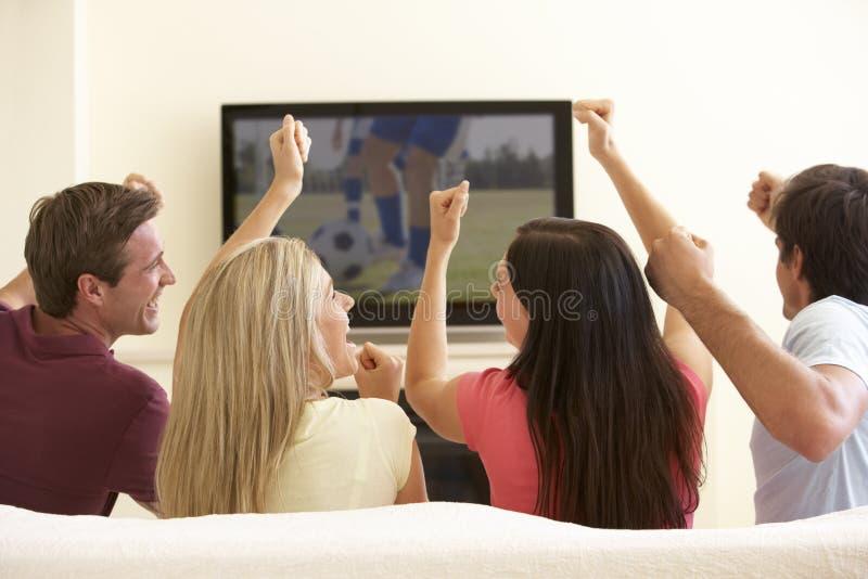 Grupp av vänner som hemma håller ögonen på Widescreen TV royaltyfria bilder