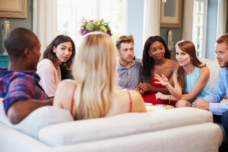 Grupp av vänner som hemma kopplar av på Sofa Together arkivfoton