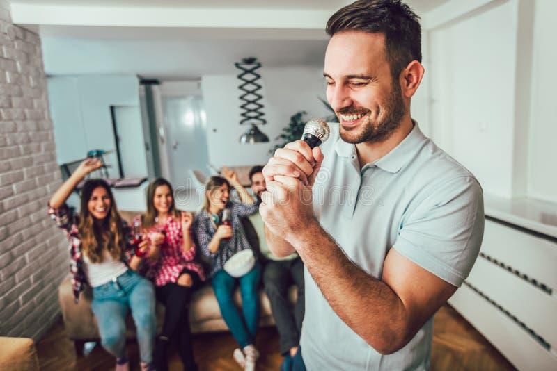 Grupp av vänner som hemma spelar karaoke arkivfoto