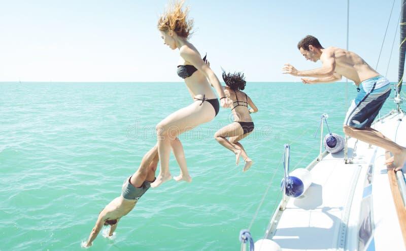 Grupp av vänner som hoppar i vattnet från fartyget royaltyfri bild