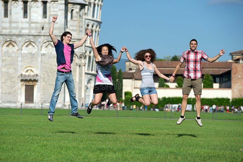 Grupp av vänner som hoppar med Pisa det lutande tornet royaltyfri fotografi