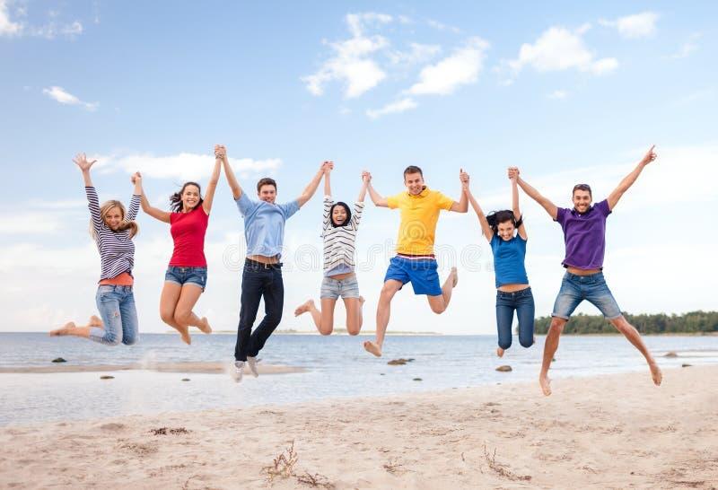 Grupp av vänner som hoppar på stranden royaltyfri bild