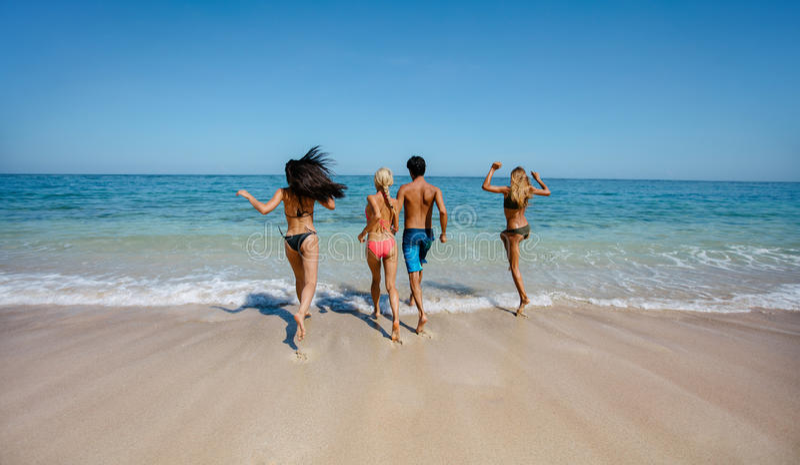 Grupp av vänner som kör in i havsvatten royaltyfri foto