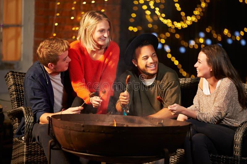 Grupp av vänner som lagar mat korvar vid Firepit royaltyfri bild