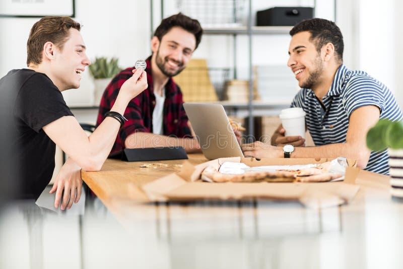 Grupp av vänner som ler och ser ett tecken i ett kontor fotografering för bildbyråer