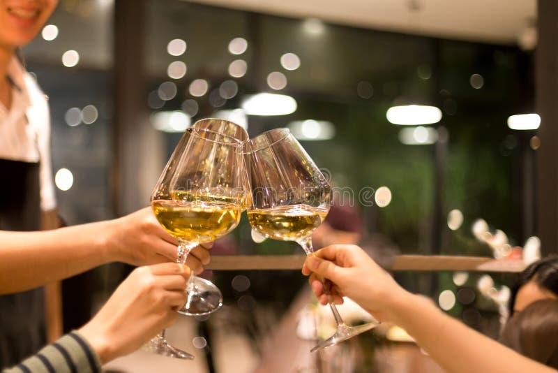 Grupp av vänner som lyfter ett rostat bröd med exponeringsglas av vitt vin royaltyfria foton