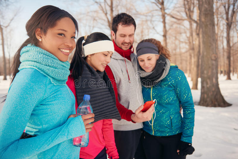 Grupp av vänner som lyssnar till musik i den insnöade vintern royaltyfri foto