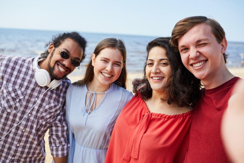 Grupp av vänner som poserar vid havet royaltyfria bilder