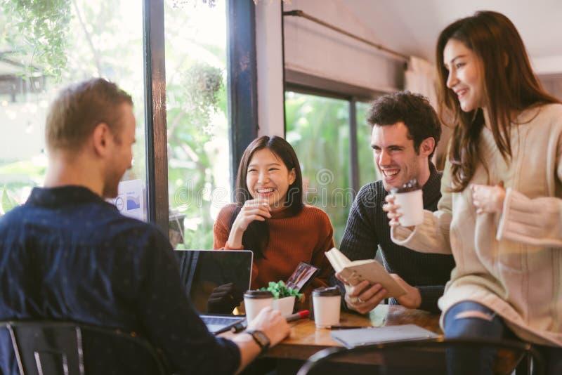 Grupp av vänner som pratar och använder bärbara datorn i kafé på coffee shopkafét i universitet som tillsammans talar och skratta royaltyfria bilder